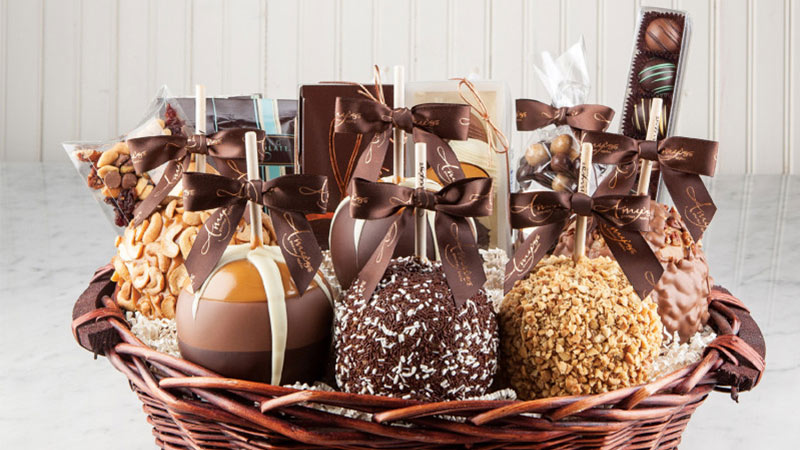 Fancy caramel apples and candies in a woven basket.