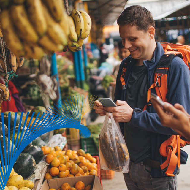 Man buying fruit using his mobile phone at an outdoor market.