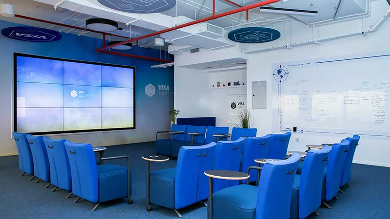 A meeting room at the Dubai innovation center that includes a monitor wall and a white board.